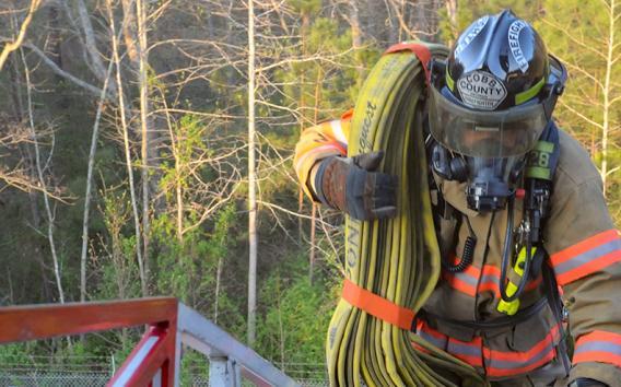 Firefighter hauling hoses